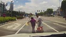 广州:老人被困车流 司机拦车助其过路